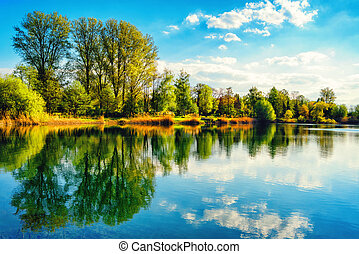 Tranquil lakeshore landscape with blue sky and water -...