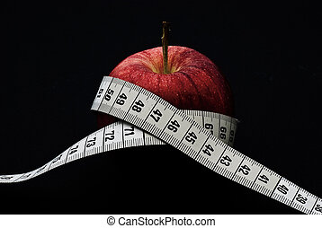 Red apple with measuring tape - A delicious red apple with...