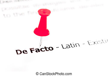 Words DE FACTO pinned on white paper with red pushpin,...