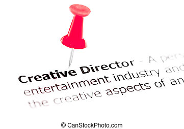 Words CREATIVE DIRECTOR pinned on white paper with red...