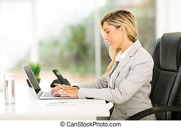 businesswoman working on laptop computer - professional...