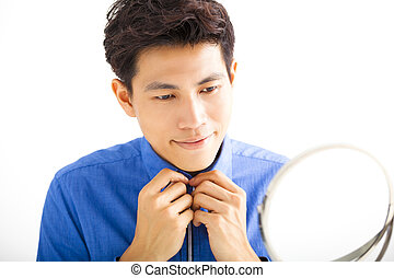Smiling handsome man fixing his tie in front of mirror