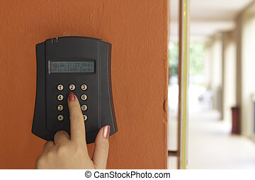 A female hand arming a burglar alarm system mounted on a...