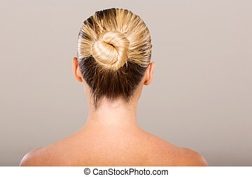 young woman with hair bun - rear view of young woman with...