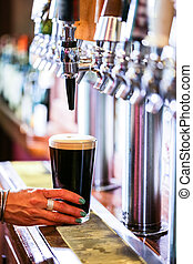 Draft beer - Bartender pouring draft beer in the bar.