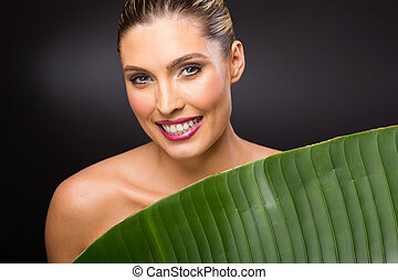 young woman standing behind green leaf