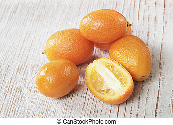 Kumquat - Small orange kumquat fruit on wood