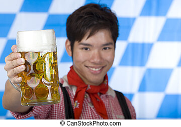 Happy man smiles and cheers with Oktoberfest beer stein Mass...
