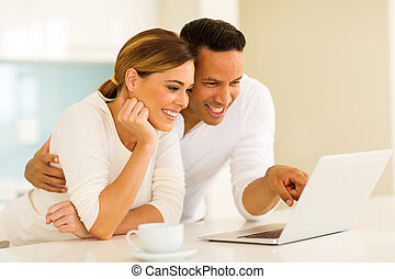 couple using laptop computer in the kitchen - happy couple...