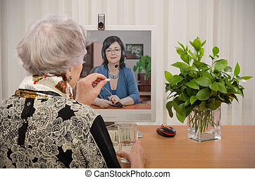 Doctor-patient online relationship - Senior woman taking a...