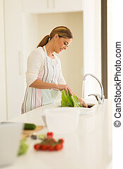 housewife washing vegetables in the kitchen - beautiful...
