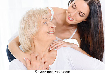 Pretty woman embracing old lady - Pleasant time Attractive...
