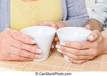 Close up of cups held by women - Nice manicure Close-up of...
