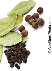 cooking herbs. bay leafs and black pepper closeup on white...