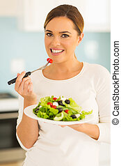 woman eating salad - portrait of pretty woman eating salad