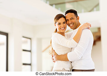couple hugging in their new house - happy couple hugging in...