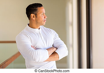 thoughtful mid age man with arms crossed
