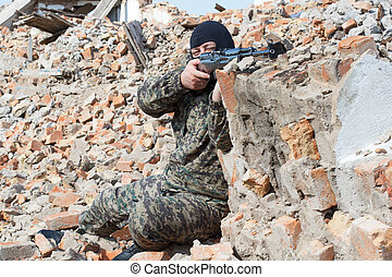 Military camouflage with a rifle on a background of bombed...