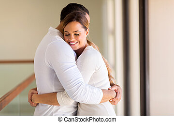 woman hugging her husband - happy woman hugging her husband
