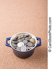Malaysian Coins - Malaysian coins in a blue pot on cork...
