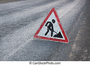 triangular road sign roadwork on asphalt