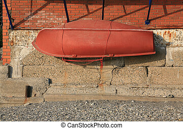 orange lifeboat attached to concrete wall