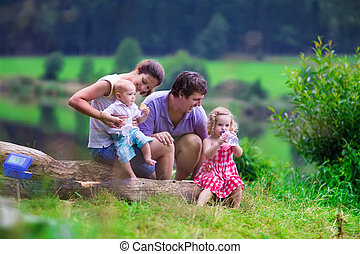Young family with kids hiking at a lake - Family on summer...