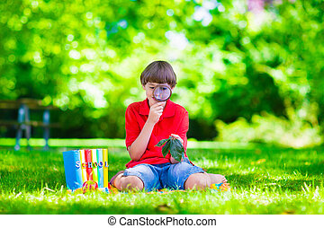 Child in school yard with magnifying glass - Happy school...