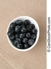 A bowl of blue berries - Top view of a bowl of blue berries.
