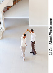 couple dancing at their new home - overhead view of couple...