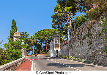 Monaco-Ville, Monaco. - Street with green trees under blue...