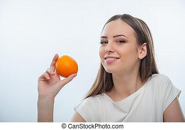 Pretty young girl is showing fresh fruit - Beautiful woman...
