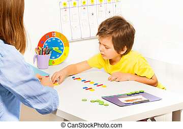 Concentrated boy putts colorful coins during ABA -...