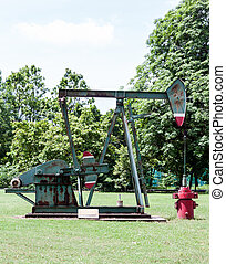 Old oil pump in the exhibition field of urban park.
