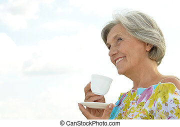 happy elderly woman against the sky with a cup of tea