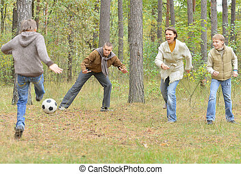 playing football - Family of four playing football in autumn...