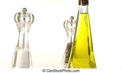 cruet, salt shaker and pepper shaker rotating over white...