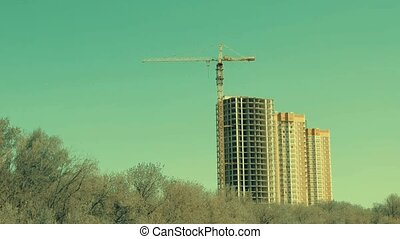Tower crane on a construction site before buildings and...