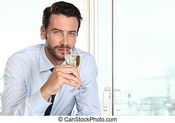 beautiful man drinking champagne with intriguing look and haughty