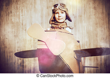 aviator - Cute dreamer boy playing with a cardboard airplane...