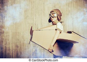 first flight - Cute dreamer boy playing with a cardboard...