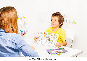 Happy boy holding the drawing with colored shapes with his...