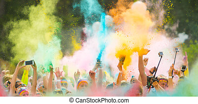 Colorrun competitors in detail of hands throwing colored...