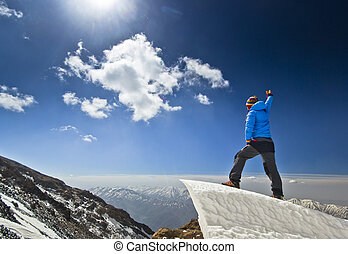 man standing on a snow cornice in mountain sunrise - happy...