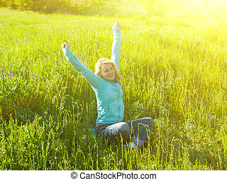 Portrait of young beautiful girl in a green field at sunset.