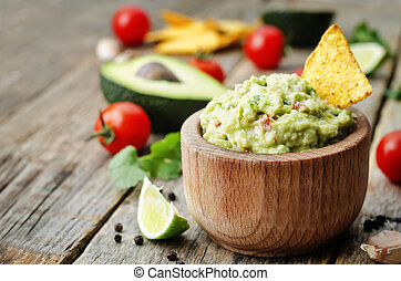 guacamole with corn chips on a dark wood background. the...