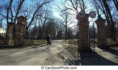 mother stroller park gate - Nanny woman with blue stroller...