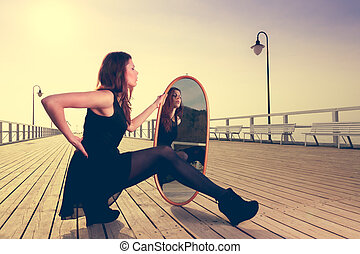 thoughtful woman looks at reflection in mirror - Solitude...