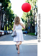 Curly blond girl with big red ballon