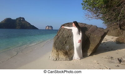 bride leans on rock  and looks aside at beach